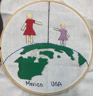 A embriodery of a globe with two people trying to hold hands on different sides of a divide.