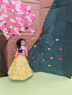 A doll made of paper with a pink tree above.