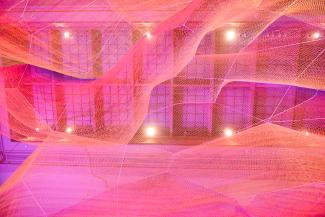 A photograph of colorful mesh hung from the ceiling inside the Grand Salon at the Renwick Gallery.