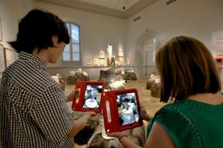 A photograph of two people holding Ipads with artwork on them.