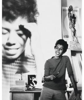 A photograph of a woman standing with an enlarged photograph behind her of herself.