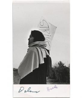 A photograph of a woman holding a protest sign with a scarf.