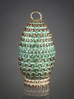 A oval artwork with green and gold material woven into it.