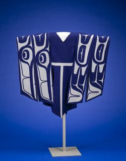 A blue dress handing on a stand with sleeves made of white and blue material depicting wings.