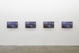 A photograph of four tv screens in an art gallery.