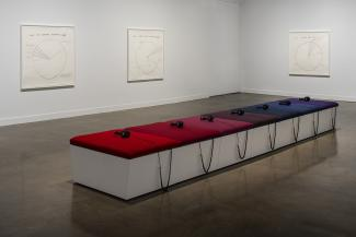 A photograph of a gallery space with artwork on the walls and a bench with headphones