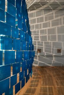 An installation photograph of small cloth indigo hanging from the ceiling.