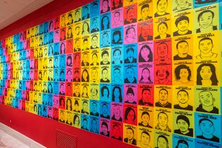 A photograph of a gallery wall with colorful artwork