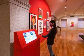 A photograph of a person using a kiosk inside an art museum