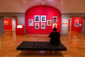 A photograph inside an art gallery with a person in the foreground.