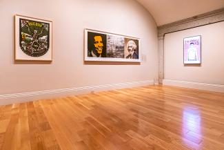A photograph with artwork on the wall inside a gallery.