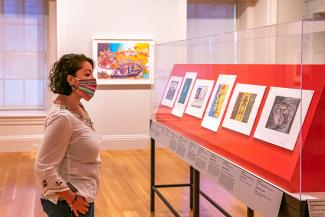 A photograph of a woman looking at artwork
