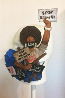 An applique sculpture of a woman in a mask holding protest signs.