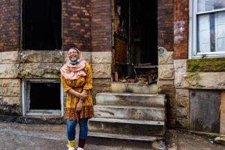 An African American girl wearing a rose-colored hijab stands, smiling, in front of a stone and brick rowhome.
