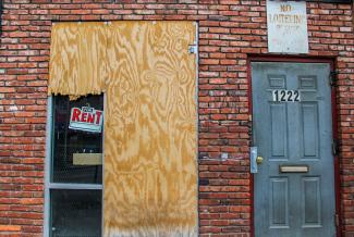 """The exterior of a building with two doors, one boarded up with a """"For Rent"""" sign to the left and one with a """"No Loitering"""" sign above."""