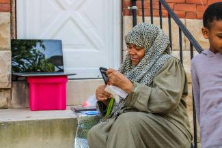 An African American woman wearing a leopard print hijab looks at her phone and smiles. Resting on the top step to her right is a laptop. A boy stands half inside the frame to her left.