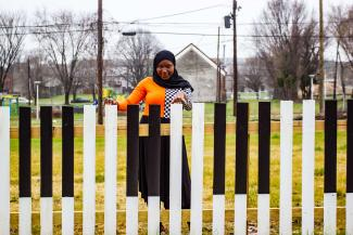 An African American girl wearing a black hijab looks directly at the camera, smiling. In front of her is a fence painted to resenble piano keys. Her fingers rest atop the fence.