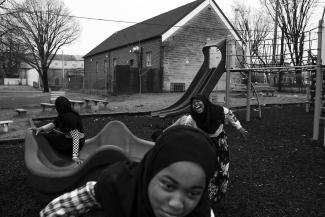 A black and white photos of three African American girls wearing dark hijabs laugh and play on playground equipment.