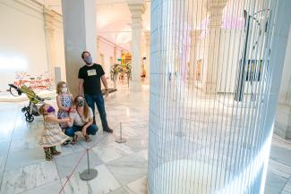 A man, woman, and two small children look upon an LED sculpture by Jenny Holzer