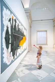 Two small girls look upon a massive painting on the third floor of the Smithsonian American Art Museum