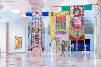 A visitor stands under multiple hanging artworks on the third floor of the Smithsonian American Art Museum