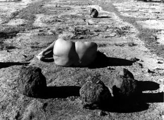 Black and white photograph of woman laying on desert ground with her backside facing the viewer
