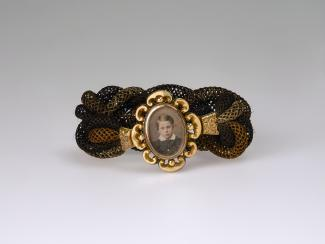 A hairband with the face of a young boy surrounded by a gold frame