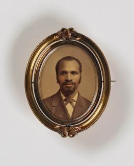 A gilded frame houses a photograph of a man with a goatee