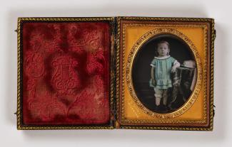 A sixth-plate daguerreotype shows a young child in a blue shirt standing