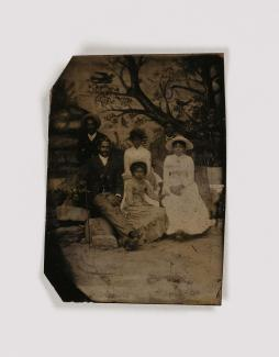 A tintype photograph of family standing in front of a tree
