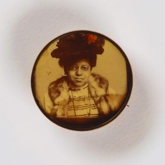 A jewelry pin showing woman in a large black hat staring directly