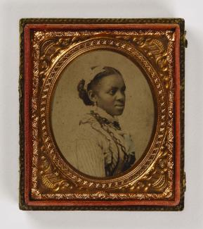 A black woman is shown in profile surrounded by a gilded frame