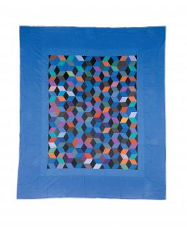 A quilt in the tumbling blocks pattern with a blue border.