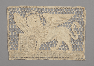 A rectangular piece of lace depicting a winged lion with a halo around its head holding a book, possibly the Bible.