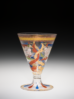 A transparent goblet with opaque red, yellow, and blue patterns.