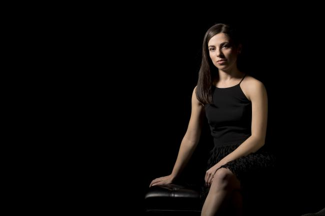 A photograph of a girl sitting in a black dress.