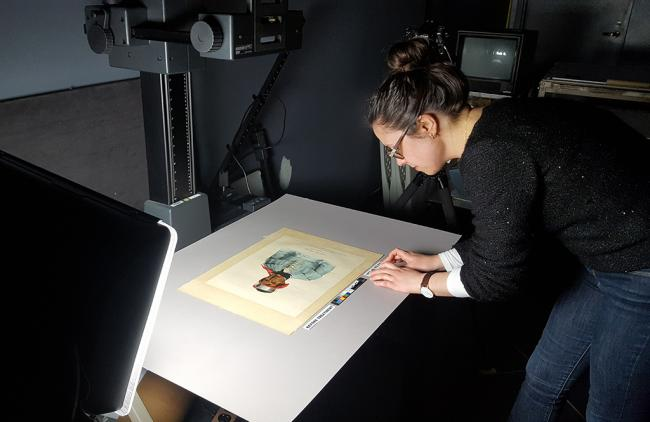 A conservator inspecting a work of art at the Lunder Conservation Center