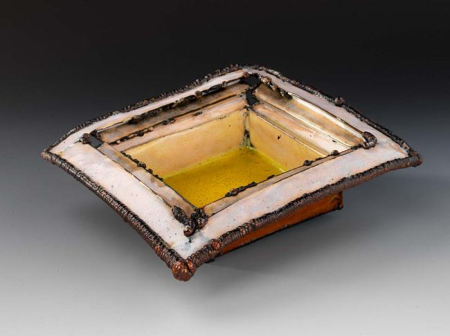 Ceramic square structure with yellow interior base with lighter top and red exterior coloring.