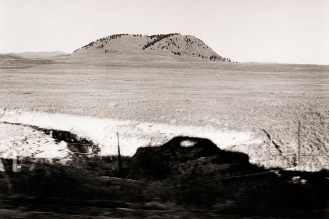 A photograph of a Colorado landscape with a mountain taken by automobile.