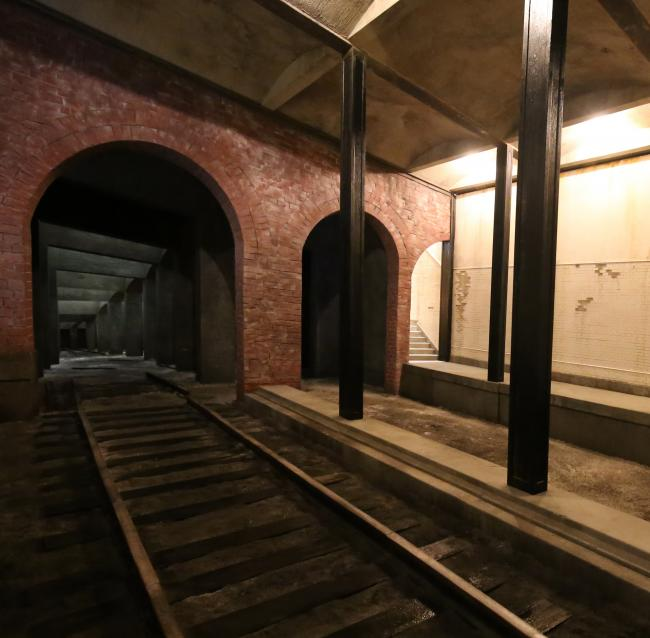 A photograph of Rick Araluce's Final Stop structure depicting a train station platform with tracks and tunnels.