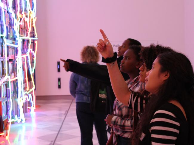 A picture of k-12 students in front of Nam June Paik's Superhighway.