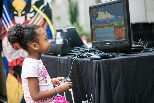 A photograph of a little girl playing a video game at SAAM Arcade.
