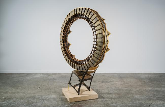 This is a picture of a circular sculpture piece resting on a chair.
