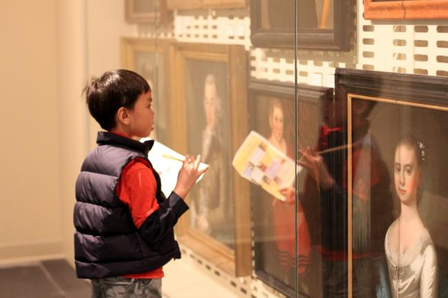 A boy doing a scavenger hunt at the Luce Foundation Center.