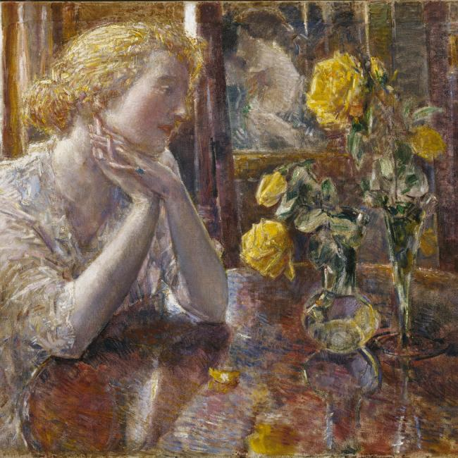 A woman sitting at a table looking at yellow flowers.