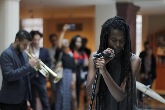 A woman singing into a microphone with a man playing trumpet behind her.