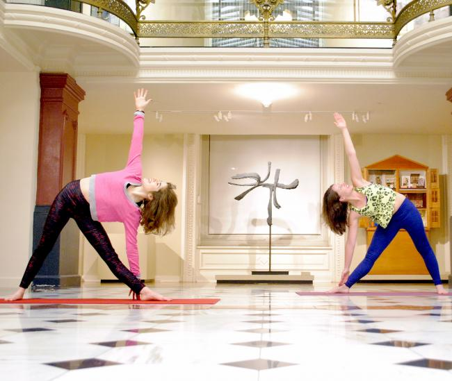 Two women stretching on yoga mats in the Luce Foundation Center.