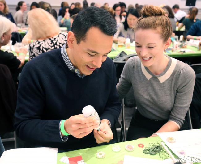 A photograph of a man and woman smiling while crafting at a table.