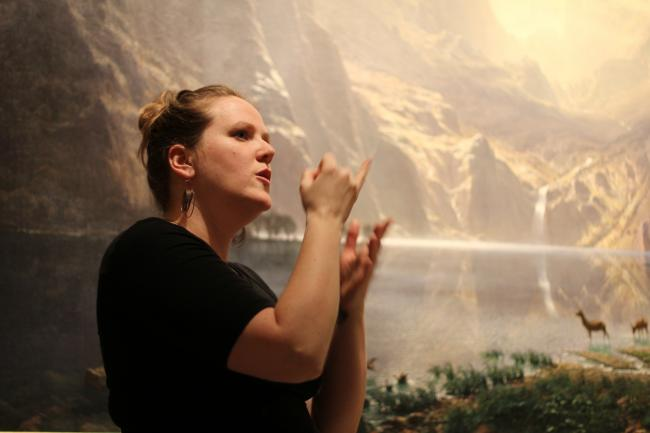 A photograph of a woman using her hands to sign in front of a landscape painting.