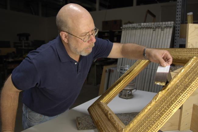A photograph of a man painting a gold frame inside a room.
